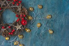 Traditional Christmas wreath from twigs with red decorations and lighted garland. Top view on traditional Christmas wreath from twigs, stars and pine cones with royalty free stock photo