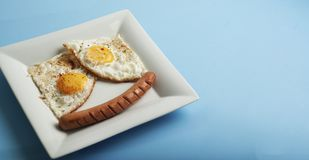 Traditional Clasic Breakfast Fried Eggs and Sausage on a white Square Porcelain Plate. Isoalted on Blue Background. Banner Copy Sp royalty free stock images