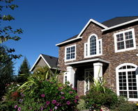 Traditional Classic home. Classic 2 story home with clear blue sky and flowers in the foreground Stock Images