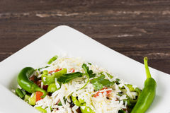 Traditional classic Shopska salad with tomatoes, peppers, cucumbers and cheese in white dish on grey wooden table. Royalty Free Stock Photography