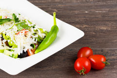 Traditional classic Shopska salad with tomatoes, peppers, cucumbers and cheese in white dish on grey wooden table. Royalty Free Stock Images