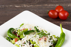 Traditional classic Shopska salad with tomatoes, peppers, cucumbers and cheese in white dish on grey wooden table. Stock Photography