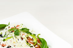 Traditional classic Shopska salad with tomatoes, peppers, cucumbers and cheese in white dish on white wooden table. Bulgarian cuis Royalty Free Stock Photography