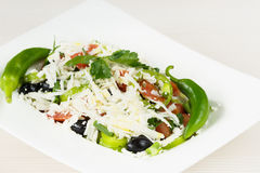 Traditional classic Shopska salad with tomatoes, peppers, cucumbers and cheese in white dish on white wooden table. Bulgarian cuis Stock Photos