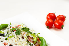 Traditional classic Shopska salad with tomatoes, peppers, cucumbers and cheese in white dish on white wooden table. Bulgarian cuis Royalty Free Stock Image