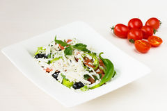 Traditional classic Shopska salad with tomatoes, peppers, cucumbers and cheese in white dish on white wooden table. Bulgarian cuis Stock Photography