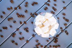 Traditional classic white Turkish delight - Eastern Turkish delicacy. Roasted coffee beans. Wooden background. Daylight stock photo
