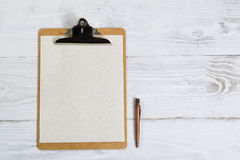 Traditional Clipboard with vintage metal pen on white desktop Royalty Free Stock Image