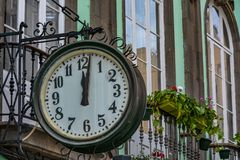 Traditional clock at a building. Showing `just after noon Royalty Free Stock Photo