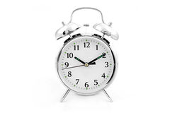 Traditional clockwork alarm clock. Silver clockwork dual bell alarm clock on a white background Royalty Free Stock Image