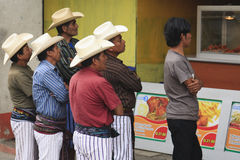 Traditional clothing in Easter in Guatemala. A group of men watch football from the street and wear traditional clothing in Easter, Santiago Atitlan, Lake Stock Photos