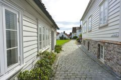 Traditional cobblestone street with wooden houses in the old town of Stavanger, Norway. Small cobblestone street with traditional white painted wooden houses on Royalty Free Stock Photography