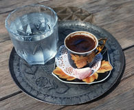 Traditional Coffee. Mug on a silver tray with a glass of water Royalty Free Stock Images