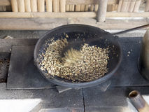 Traditional coffee beans roasting. In metal basin with spoon blurry due to movement Royalty Free Stock Photography