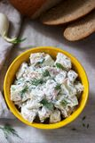 Traditional cold potato salad with onions and herbs on a linen tablecloth background. Rustic style. Selective focus stock photography