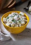 Traditional cold potato salad with onions and herbs on a linen tablecloth background. Rustic style. Selective focus stock photo