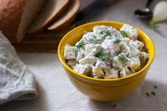 Traditional cold potato salad with onions and herbs on a linen tablecloth background. Rustic style. Selective focus stock image