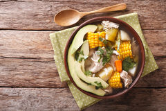 Traditional Colombian ajiaco soup close up in a bowl. horizontal. Traditional Colombian ajiaco soup close up in a bowl on the table. horizontal view from above Stock Image