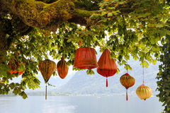 Traditional colorful Asian lanterns common in China, Korea, Japan, Vietnam, Thailand hanging. Below an old tree with green leaves against a lake and mountain Stock Photography