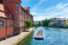Traditional colorful houses in La Petite, with tourists taking a boat ride along traditional colorful houses on idyllic river Lauc. H in summer, Colmar, Alsace Stock Photography