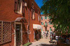 Traditional colorful houses in ocher and people in Roussillon.