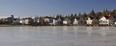 Traditional colorful islanian houses on the shores of a frozen lake in Reykjavik royalty free stock photography