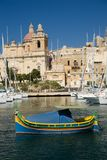 Traditional colorful maltese fishing boat in harbor of Malta. Malta, typical landscape, traditional fishing boat in harbour, and historical buildings behind Royalty Free Stock Photos