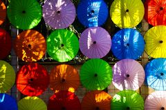 Traditional colorful paper umbrellas hanging in a row on wall in the evening sun in Chiang Mai, Thailand royalty free stock images