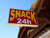 Snacks 24 hours sign hanging in front of a restaurant. Traditional colorful Snacks 24 hours sign hanging in front of a restaurant clear sky background royalty free stock photo