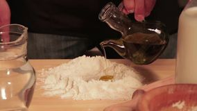 Baker adds olive oil to the dough. Traditional cook adds olive oil to the bread dough in the kitchen stock video footage