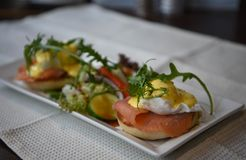 Healthy food photography image of traditional homemade eggs royale breakfast with fresh salmon and poached eggs on a dark table. Traditional cooked and served Stock Image