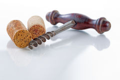 Traditional corkscrew with corks on glass table stock image