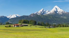 Traditional Alpine spring panoramic landscape in Berchtesgaden with Watzmann mount and flowering meadow Stock Photos