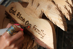 Traditional Crafting. A Lebanese woman carving God bless our family on a wooden cedar shape in a Lebanese traditional craft shop Royalty Free Stock Photo