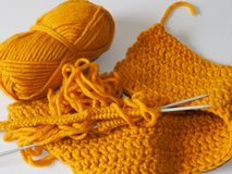Traditional crafts such as knitting of wool or other yarn with knitting needles. Mustard color thread and a spoke for knitting. Traditional crafts such as royalty free stock images
