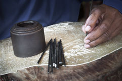 Traditional craftsman carving wood. Making indonesian puppets Stock Photos