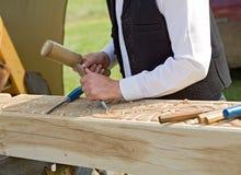 Traditional craftsman carving wood. Column at a fair Royalty Free Stock Image