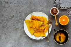 Traditional Crepes Suzette. Delicious Crepes Suzette. Flat-lay of thin pancakes with orange sauce over grey concrete table background. Top view - Image royalty free stock images