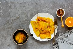 Traditional Crepes Suzette. Crepes Suzette. Flat lay of thin pancakes with orange sauce over grey concrete table background. Top view - Image stock photography