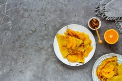 Traditional Crepes Suzette. Flat-lay of thin pancakes with orange sauce over grey concrete table background. Top view - Image royalty free stock photo