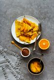 Traditional Crepes Suzette. Crepes Suzette on plate flat lay. Thin pancakes with orange sauce over grey concrete table background. Top view - Image stock photos