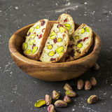 Traditional crispy Italian biscotti or cantuchini crackers with pistachios and dried cranberries in a bowl of olve wood