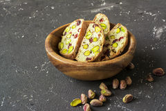 Traditional crispy Italian biscotti or cantuchini crackers with pistachios and dried cranberries in a bowl of olve wood Royalty Free Stock Photo
