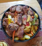 Traditional croatian dish Peka view. Meat and vegetables in iron cover under warm glow stock photography