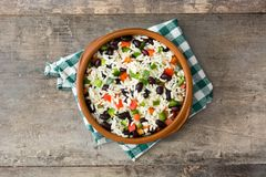 Traditional cuban rice, black beans and pepper on wooden table background. Moros y cristianos. Top view Stock Photo