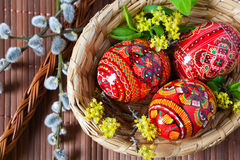 Traditional Czech easter decoration - colorful painted eggs in w. Traditional Czech easter decoration - colorful painted red eggs in wicker nest with pussycats Royalty Free Stock Images