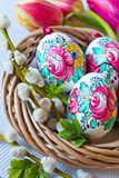 Traditional Czech easter decoration - colorful painted eggs in wicker nest with pussycats Royalty Free Stock Photography