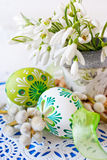 Traditional Czech easter decoration - flowerpot with snowdrops flowers and decorated green eggs with pussycats Stock Image