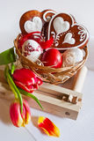 Traditional Czech easter decoration - homemade gingerbread hearts cakes with tulip flowers, painted eggs and ratchet Stock Image