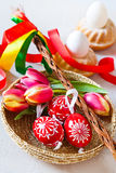 Traditional Czech easter decoration - regional whip with ribbons. With tulip and decorated red eggs in the wicker scuttle. Spring easter holiday arrangement Stock Photos